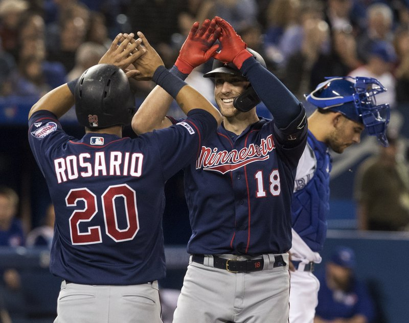 Minnesota Twins' Mitch Garver (18) high-fives teammate Eddie Rosario (20) after Garver hit a two-run home run against the Toronto Blue Jays in the sixth inning of a baseball game in Toronto, Tuesday, May 7, 2019. (Fred Thornhill/The Canadian Press via AP)