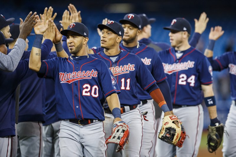 Minnesota Twins' Eddie Rosario, left and, Jorge Polanco center, celebrate after defeating the Toronto Blue Jays in baseball game action in Toronto, Monday, May 6, 2019. (Mark Blinch/The Canadian Press via AP)