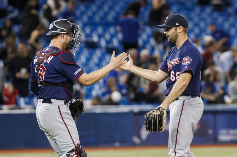 Minnesota Twins Matt Magill, right, celebrates with teammate Mitch Garver after they defeated the Toronto Blue Jays in baseball game action in Toronto, Monday, May 6, 2019. (Mark Blinch/The Canadian Press via AP)