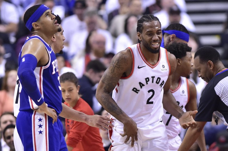Toronto Raptors forward Kawhi Leonard (2) smiles as Philadelphia 76ers forward Tobias Harris (33) looks at the scoreboard during the first half of Game 5 of an NBA basketball second-round playoff series, Tuesday, May 7, 2019, in Toronto. (Frank Gunn/The Canadian Press via AP)