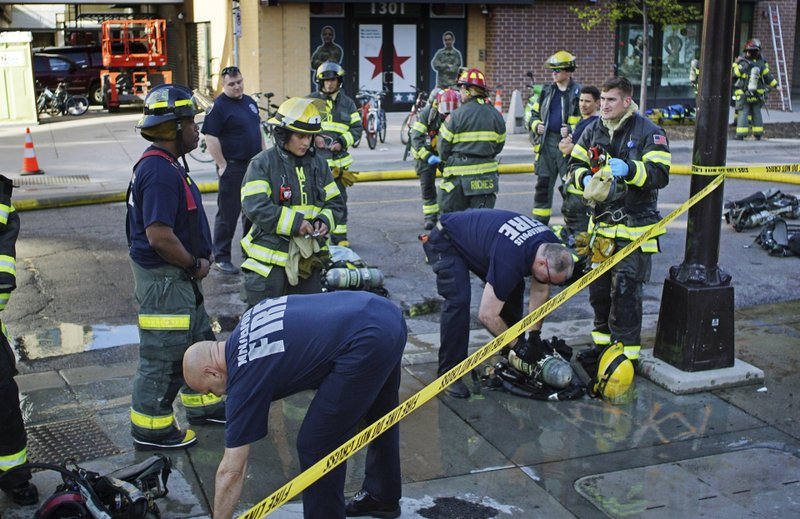 Firefighters work the scene as they were evacuating a Dinkytown apartment building after a report of a hazardous materials incident in Minneapolis on Tuesday, May 7, 2019. (Richard Tsong-Taatarii/Star Tribune via AP)