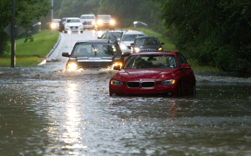 Vehicles wade through flooded Kingwood Drive as thunderstorms hit the Kingwood area Tuesday, May 7, 2019, in Kingwood, Texas. (Jason Fochtman/Houston Chronicle via AP)