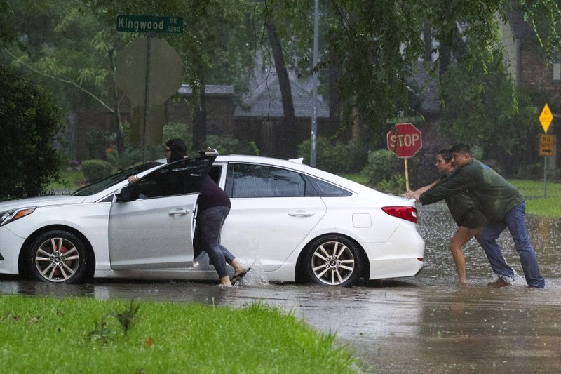 Residents push a stalled car as thunderstorms hit the Kingwood area flooding parts of Kingwood Drive, Tuesday, May 7, 2019, in Kingwood, Texas. (Jason Fochtman/Houston Chronicle via AP)