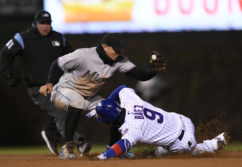 Chicago Cubs' Javier Baez (9) is tagged out at second base by Miami Marlins shortstop Miguel Rojas left, while attempting a double during the sixth inning of a baseball game, Tuesday, May 7, 2019, in Chicago. (AP Photo/Paul Beaty)