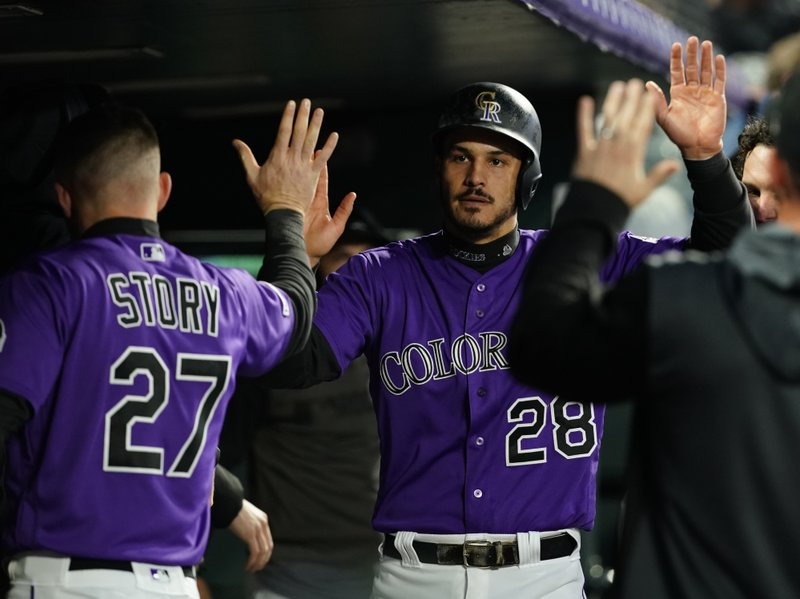 Colorado Rockies' Nolan Arenado is congratulated by teammates in the dugout after scoring a run against the San Francisco Giants during the fourth inning of a baseball game, Tuesday, May 7, 2019, in Denver. (AP Photo/Jack Dempsey)