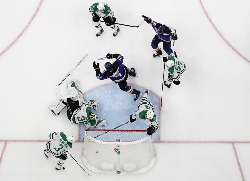 St. Louis Blues' Pat Maroon (7) and Robert Thomas (18) celebrate a score by Maroon, as Dallas Stars' John Klingberg (3), Ben Bishop (30), Miro Heiskanen (4) and Justin Dowling (37) react during the second overtime in Game 7 of an NHL second-round hockey playoff series Tuesday, May 7, 2019, in St. (AP Photo/Jeff Roberson)