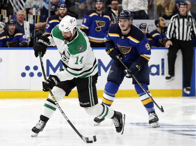 Dallas Stars' Jamie Benn (14) shoots the puck as St. Louis Blues' Sammy Blais (9) looks on during the second overtime period in Game 7 of an NHL second-round hockey playoff series, Tuesday, May 7, 2019, in St. (AP Photo/Jeff Roberson)