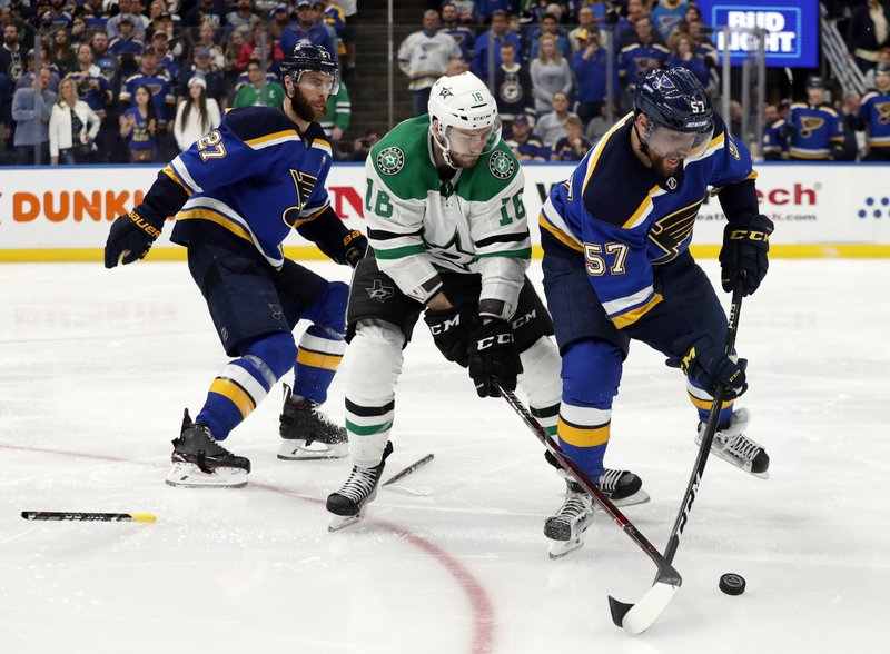 St. Louis Blues' Alex Pietrangelo (27) drops his broken stick as David Perron (57) attempts to control a loose puck in front of Dallas Stars' Jason Dickinson (16) during the second overtime period in Game 7 of an NHL second-round hockey playoff series, Tuesday, May 7, 2019, in St. (AP Photo/Jeff Roberson)