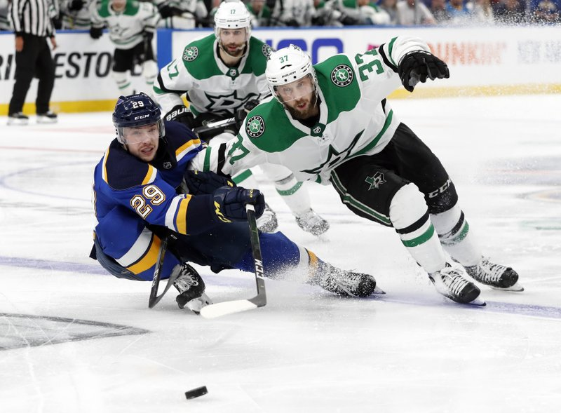 St. Louis Blues' Vince Dunn (29) and Dallas Stars' Justin Dowling (37) move to control the puck as Andrew Cogliano, rear, looks on during the second overtime period in Game 7 of an NHL second-round hockey playoff series, Tuesday, May 7, 2019, in St. (AP Photo/Jeff Roberson)