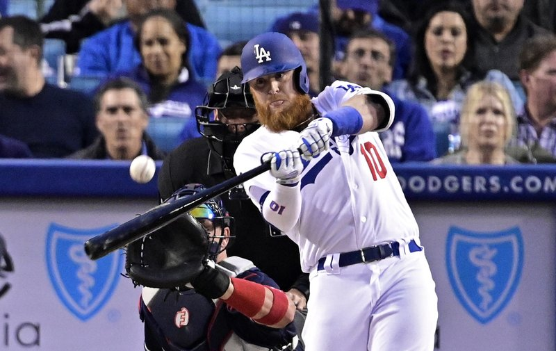 Los Angeles Dodgers' Justin Turner hits a solo home run as Atlanta Braves catcher Tyler Flowers watches along with home plate umpire Andy Fletcher during the first inning of a baseball game, Tuesday, May 7, 2019, in Los Angeles. (AP Photo/Mark J. Terrill)