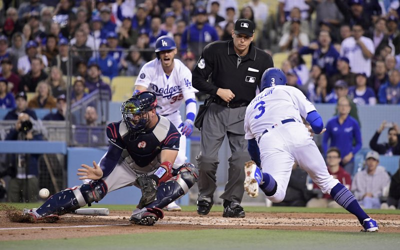 Los Angeles Dodgers' Chris Taylor, right, scores under the tag of Atlanta Braves catcher Tyler Flowers, left, on a single by Max Muncy as Cody Bellinger, left, and home plate umpire Jeff Nelson watch during the first inning of a baseball game, Tuesday, May 7, 2019, in Los Angeles. (AP Photo/Mark J. Terrill)