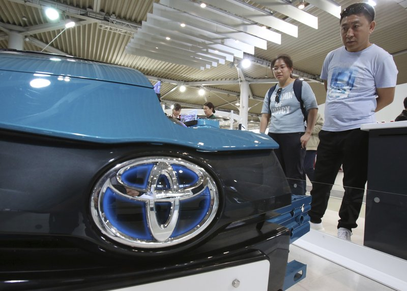 Visitors inspect Car at Toyota showroom in Tokyo, Wednesday, May 8, 2019. Japan's top automaker Toyota is reporting a 4% dip in profit for January-March after vehicle sales fell in North America. (AP Photo/Koji Sasahara)
