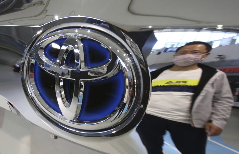A man reflected on the Car at Toyota showroom in Tokyo, Wednesday, May 8, 2019. Japan's top automaker Toyota is reporting a 4% dip in profit for January-March after vehicle sales fell in North America. (AP Photo/Koji Sasahara)