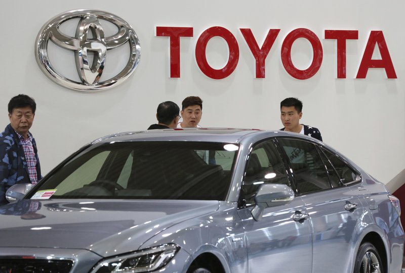 Visitors inspect a Car at Toyota showroom in Tokyo, Wednesday, May 8, 2019. Japan's top automaker Toyota is reporting a 4% dip in profit for January-March after vehicle sales fell in North America. (AP Photo/Koji Sasahara)