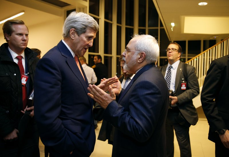 FILE - In this Jan. 16, 2016 file photo, Secretary of State John Kerry talks with Iranian Foreign Minister Mohammad Javad Zarif in Vienna, after the International Atomic Energy Agency verified that Iran has met all conditions under the nuclear deal. (Kevin Lamarque/Pool via AP, File)