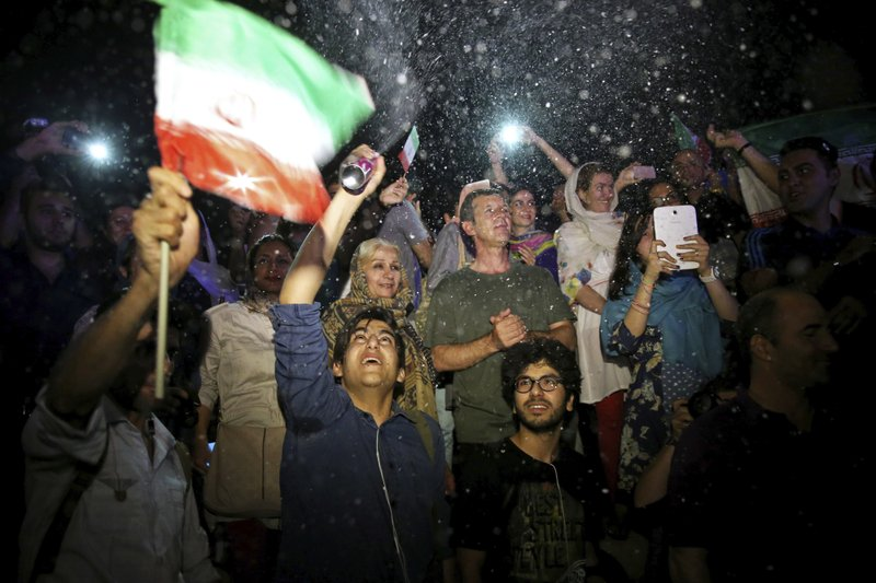 FILE - In this July 14, 2015 file photo, a group of jubilant Iranians cheer and spray artificial snow during street celebrations following a landmark nuclear deal, in Tehran, Iran. (AP Photo/Ebrahim Noroozi, File)