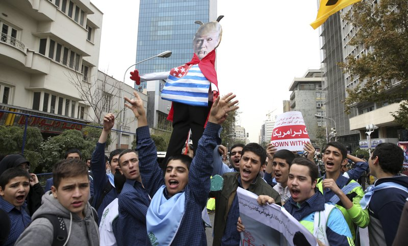 FILE- In this Nov. 4, 2017 file photo, Iranian schoolboys chant slogan while holding an effigy of U.S. (AP Photo/Vahid Salemi, File)