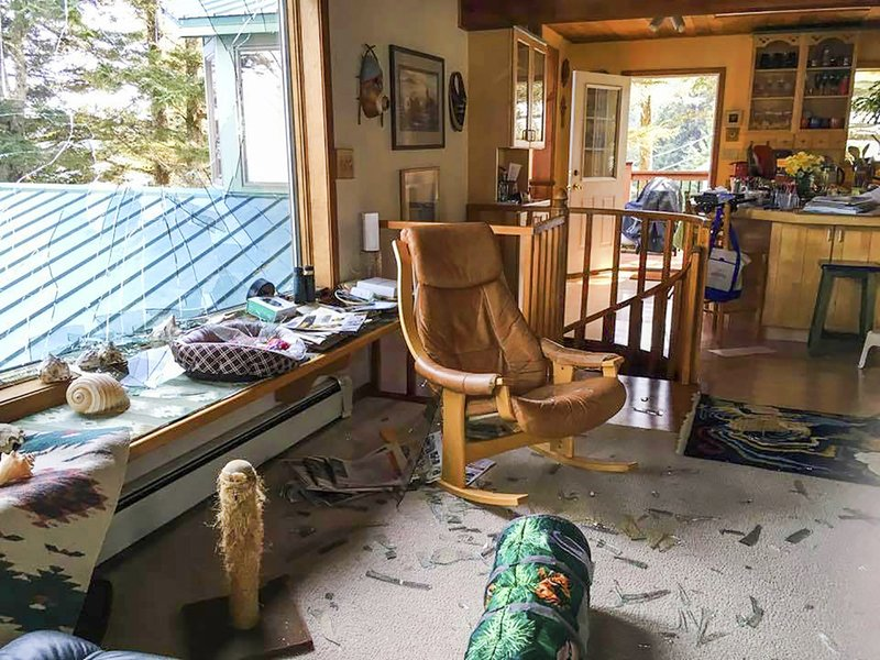 This May 4, 2019, photo shows extensive damage in the living room area of Stacy Studebaker's home in Kodiak, Alaska, after an eagle flew through a large window. The eagle carrying a 4-pound piece of halibut crashed through the front window of Stacy Studebaker's home. The homeowner suspects the eagle was being chased by another eagle and the bird misjudged its climb up a cliff. (Stacy Studebaker via AP).
