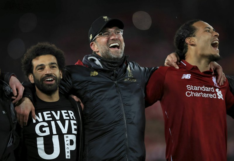 Liverpool's Mohamed Salah, left, manager Jurgen Klopp, center, and Virgil van Dijk celebrate after the Champions League Semi Final, second leg soccer match between Liverpool and Barcelona at Anfield, Liverpool, England, Tuesday, May 7, 2019. (Peter Byrne/PA via AP)
