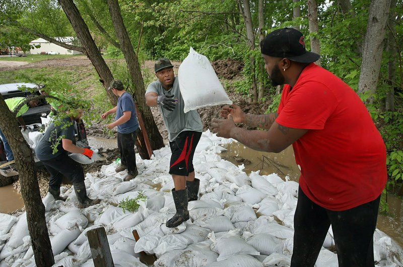 Marcus Gilbert, center,  tosses a sandbag to Herman Drones as they and other volunteers work to plug the leaks in a levee at Cherokee Lakes Campground in O'Fallon, Mo. (David Carson/St. Louis Post-Dispatch via AP)
