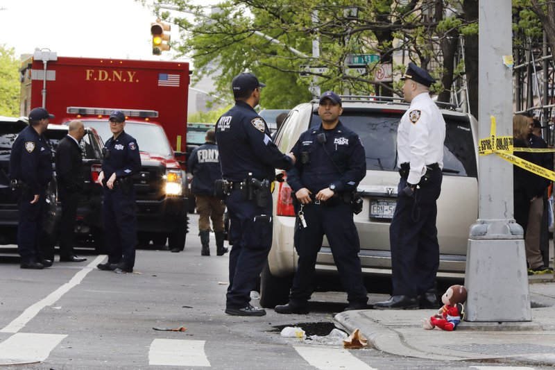 New York City police stand near a stuffed animal left by a child in front of a fire damaged building in New York's Harlem neighborhood, Wednesday, May 8, 2019. (AP Photo/Richard Drew)