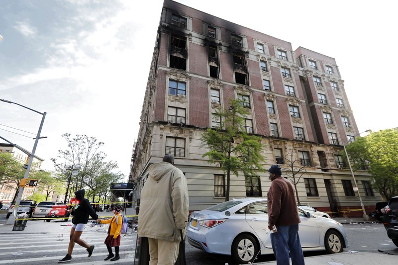 People look at a fire damaged building in New York's Harlem neighborhood, Wednesday, May 8, 2019. Six people, including four children, were killed Wednesday when an overnight fire ravaged the apartment in a city-owned Harlem building. (AP Photo/Richard Drew)