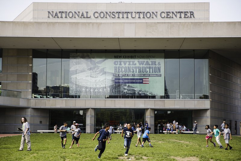 In this Tuesday, May 7, 2019 photo, children play outside the National Constitution Center in Philadelphia, which is opening a new exhibit
