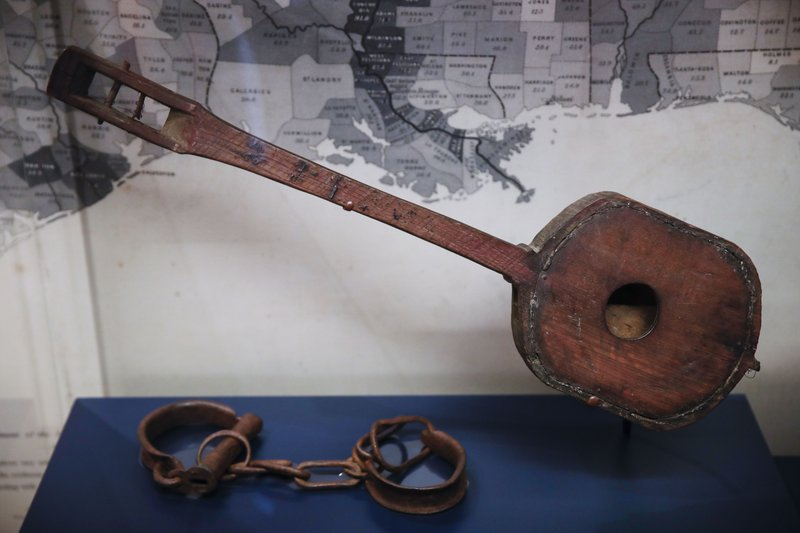 In this Tuesday, May 7, 2019 photo, shackles and a mandolin made by an enslaved person is displayed at the new exhibit