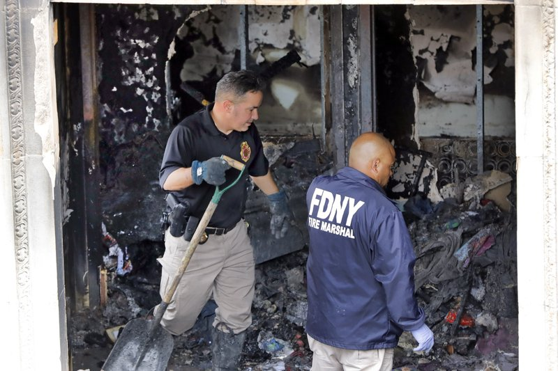 Fire marshals sift through a burned out apartment in New York's Harlem neighborhood, Wednesday, May 8, 2019. (AP Photo/Richard Drew)