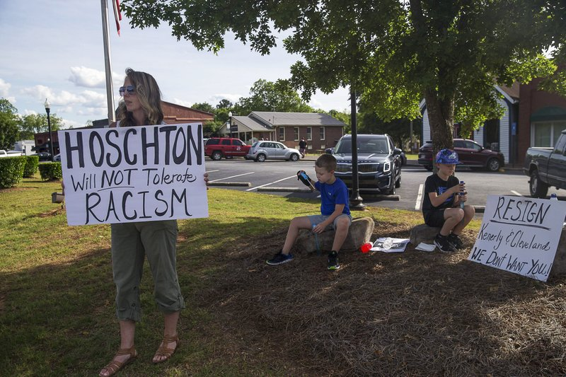 Hoschton resident Kelly Winebarger, left, protests for the resignation of Hoschton Mayor Theresa Kenerly and Councilman Jim Cleveland as her sons Ryder, center, and Knox sit quietly by the roadside in Hoschton, Ga. (Alyssa Pointer/Atlanta Journal-Constitution via AP)