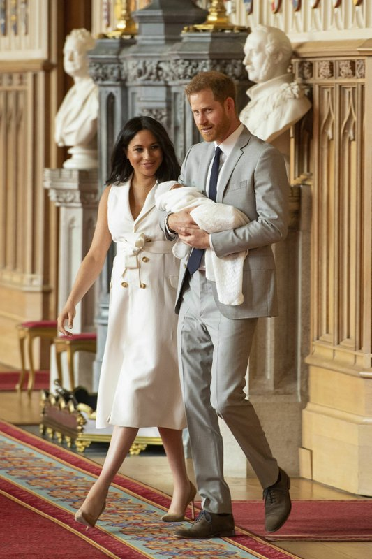 Britain's Prince Harry and Meghan, Duchess of Sussex, arrive for a photocall with their newborn son, in St George's Hall at Windsor Castle, Windsor, south England, Wednesday May 8, 2019. Baby Sussex was born Monday at 5:26 a.m. (0426 GMT; 12:26 a.m. EDT) at an as-yet-undisclosed location. (Dominic Lipinski/Pool via AP)