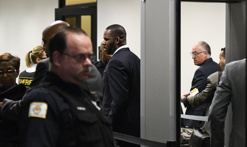 Musician R. Kelly, center, goes through security as he arrives at the Daley Center for a hearing in his child support case on Wednesday, May 8, 2019, in Chicago. (AP Photo/Matt Marton)