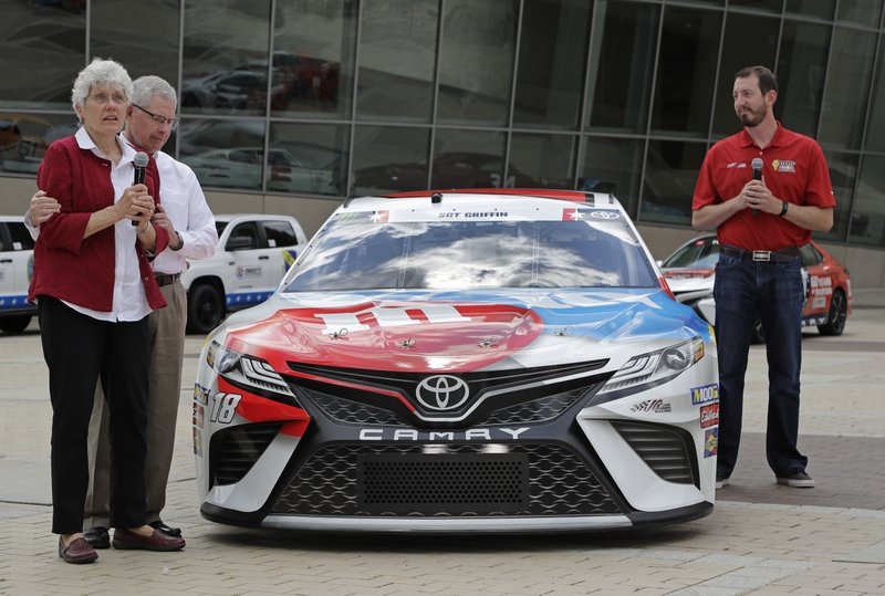 Dona Griffin, left, and Gene Griffin, second from left, stand with driver Kyle Busch, far right, after unveiling Busch's race car for the Coca-Cola 600 NASCAR Cup series auto race during a news conference in Charlotte, N. (AP Photo/Chuck Burton)