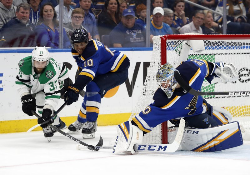 Dallas Stars center Justin Dowling (37) attempts to wrap a goal around the net as St. Louis Blues' Brayden Schenn (10) watches goaltender Jordan Binnington (50) slap the puck away during the third period in Game 7 of an NHL second-round hockey playoff series, Tuesday, May 7, 2019, in St. (AP Photo/Jeff Roberson)