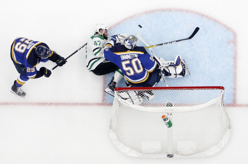 St. Louis Blues' Vince Dunn (29) looks on as Dallas Stars right wing Alexander Radulov (47) collides with goaltender Jordan Binnington (50) on a shot attempt during overtime in Game 7 of an NHL second-round hockey playoff series, Tuesday, May 7, 2019, in St. (AP Photo/Jeff Roberson)