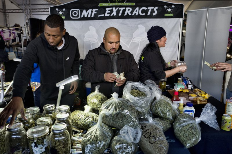 FILE - This Saturday, Dec. 29, 2018 file photo shows vendors from MF Extracts counting their intake of cash at their booth at Kushstock 6. (AP Photo/Richard Vogel, File)