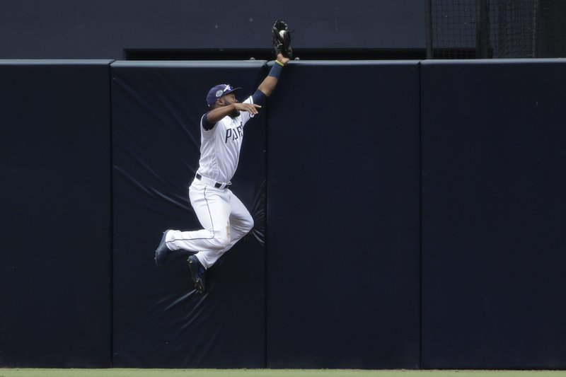 San Diego Padres center fielder Manuel Margot bobbles a catch at the wall on a double by New York Mets' Brandon Nimmo during the seventh inning of a baseball game Wednesday, May 8, 2019, in San Diego. (AP Photo/Gregory Bull)