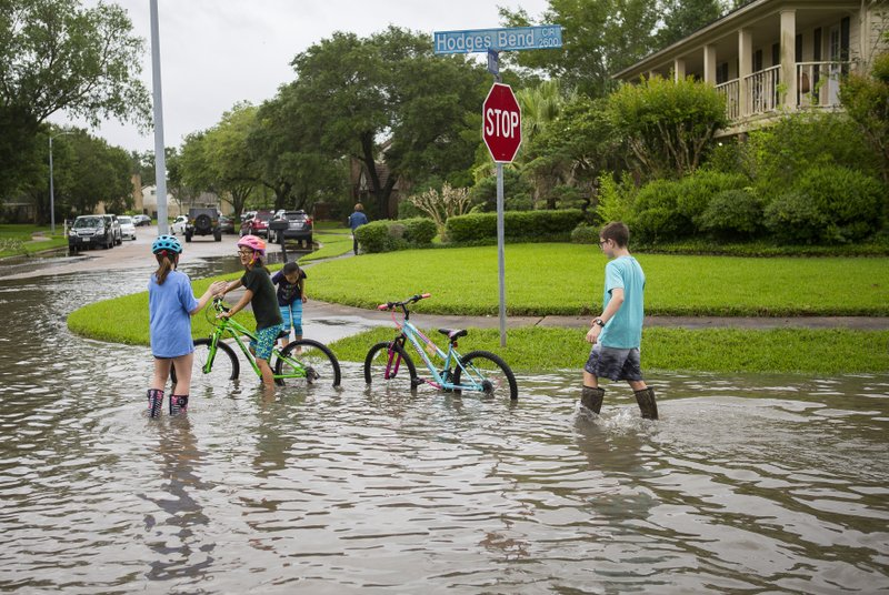 Children play in the Colony Bend neighborhood of Sugar Land, Texas, on Wednesday, May 8, 2019. Residents have been surprised that the water has not receded more quickly as it has in the past when the rain has stopped. (Mark Mulligan/Houston Chronicle via AP)