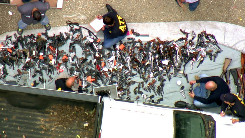 This photo from video provided by KCBS/KCAL-TV shows investigators from the U.S. Bureau of Alcohol, Tobacco, Firearms and Explosives and the police inspecting a large cache of weapons seized at a home in the affluent Holmby Hills area of Los Angeles Wednesday, May 8, 2019. (KCBS/KCAL-TV via AP)