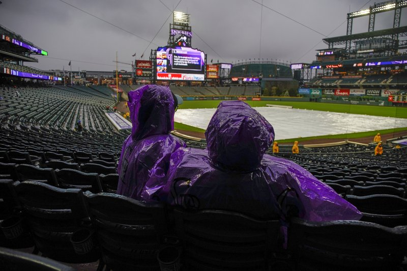 Fans sit in the rain prior to a scheduled baseball game between the San Francisco Giants and the Colorado Rockies on Wednesday, May 8, 2019, in Denver. (AP Photo/Jack Dempsey)