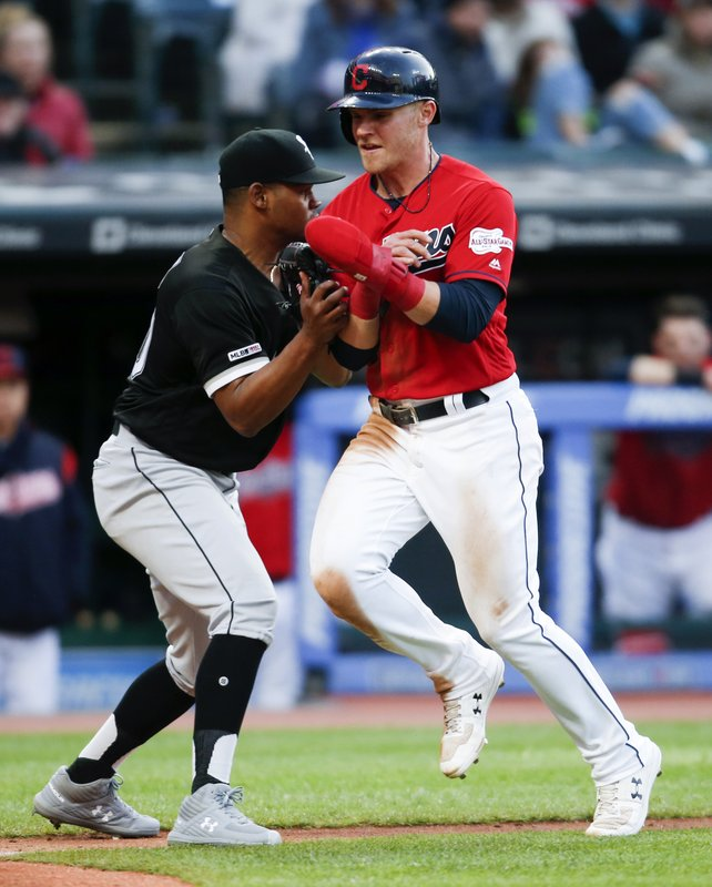Chicago White Sox starting pitcher Reynaldo Lopez tags out Cleveland Indians' Jake Bauers in a rundown between third base and home plate during the sixth inning of a baseball game Wednesday, May 8, 2019, in Cleveland. (AP Photo/Ron Schwane)