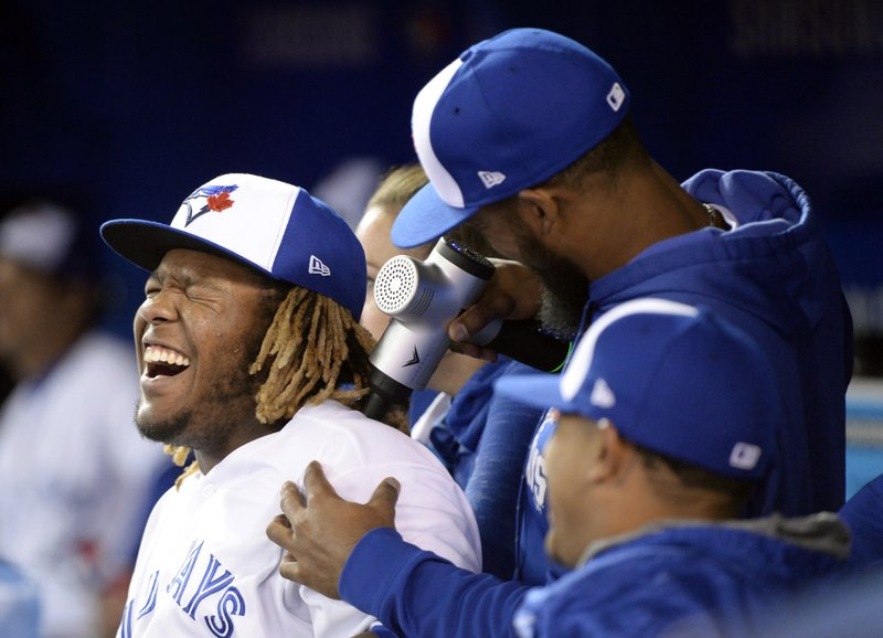 Toronto Blue Jays' Vladimir Guerrero Jr. (27) laughs as teammate Teoscar Hernandez (37) jokes around with a handheld massager during the sixth inning of a baseball game against the Minnesota Twins, Wednesday, May 8, 2019, in Toronto. (Nathan Denette/The Canadian Press via AP)