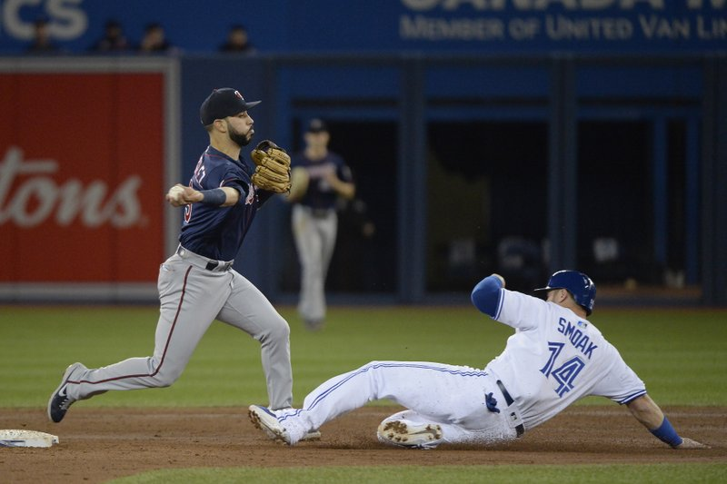 Minnesota Twins third baseman Marwin Gonzalez (9) throws to first as Toronto Blue Jays' Justin Smoak (14) is caught at second base in a rundown during the second inning of a baseball game, Wednesday, May 8, 2019, in Toronto. (Nathan Denette/The Canadian Press via AP)