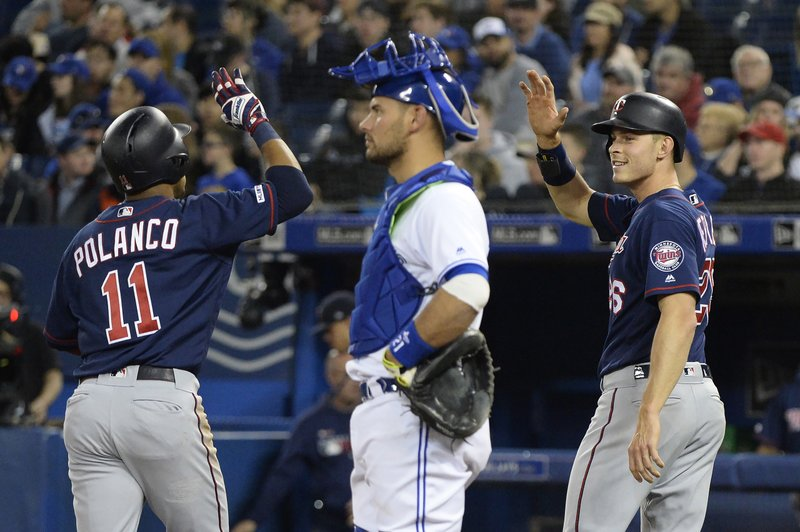 Minnesota Twins' Jorge Polanco (11) celebrates his home run with teammate Max Kepler (26) as Toronto Blue Jays catcher Luke Maile looks on during the second inning of a baseball game, Wednesday, May 8, 2019, in Toronto. (Nathan Denette/The Canadian Press via AP)
