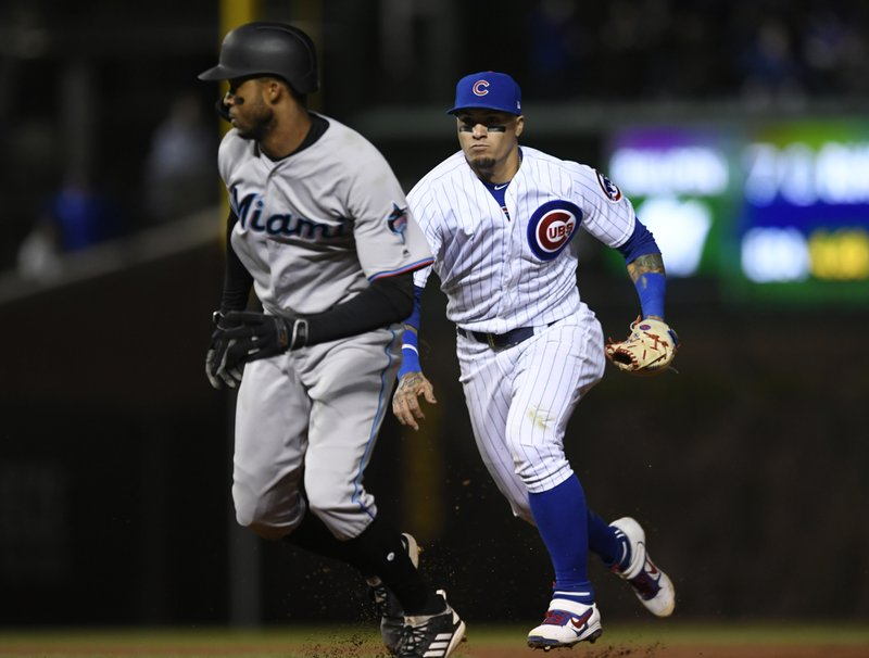 Chicago Cubs shortstop Javier Baez right, chases Miami Marlins' Rosell Herrera during a rundown between second and first during the 10th inning of a baseball game Wednesday, May 8, 2019, in Chicago. (AP Photo/Paul Beaty)
