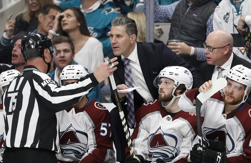 Colorado Avalanche head coach Jared Bednar, center, talks with an official after a goal by Colin Wilson was called back for a penalty during the second period of Game 7 of an NHL hockey second-round playoff series against the San Jose Sharks in San Jose, Calif. (AP Photo/Josie Lepe)
