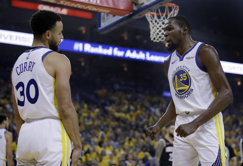 Golden State Warriors' Kevin Durant, right, speaks with Stephen Curry (30) after Curry was called for a foul during the first half of Game 5 of the team's second-round NBA basketball playoff series against the Houston Rockets on Wednesday, May 8, 2019, in Oakland, Calif. (AP Photo/Ben Margot)