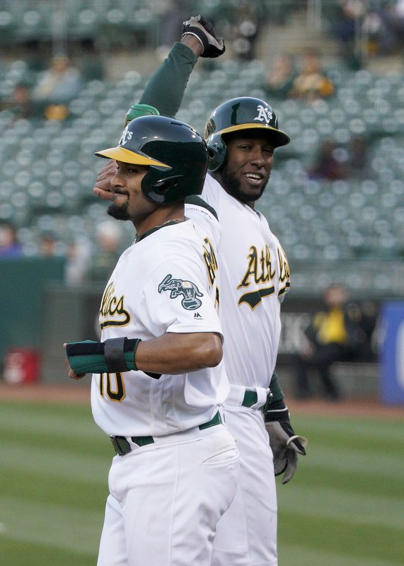 Oakland Athletics shortstop Jurickson Profar, right, is congratulated by teammate Marcus Semien (10) after hitting a two-run home run against Cincinnati Reds pitcher Sonny Gray during the first inning of a baseball game, Wednesday, May 8, 2019, in Oakland, Calif. (AP Photo/Tony Avelar)
