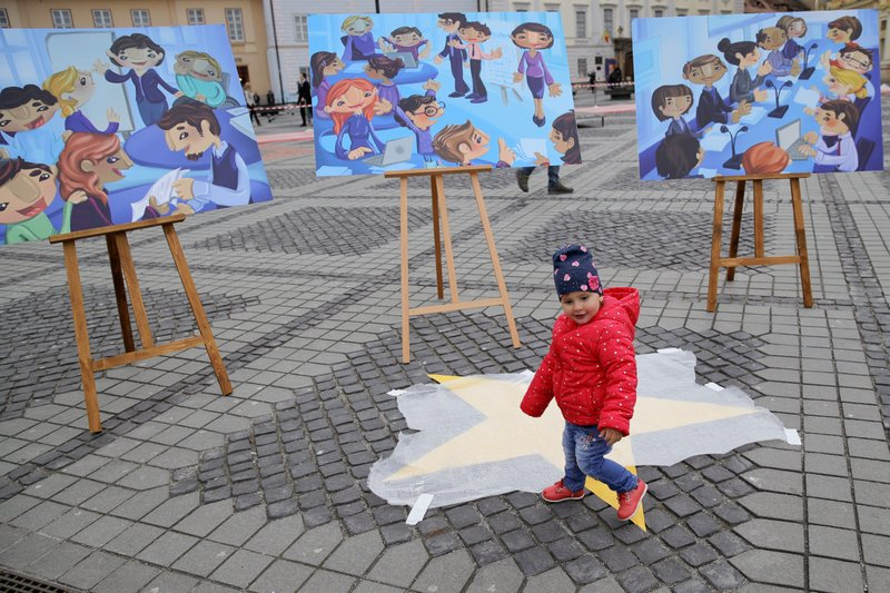 A child walks by boards depicting the creation of the Bucharest EU Children Declaration, a call for EU leaders to make child participation a priority, by children supported by UNICEF in the Piata Mare square in the Transylvanian town of Sibiu, Romania, Wednesday, May 8, 2019. (AP Photo/Vadim Ghirda)