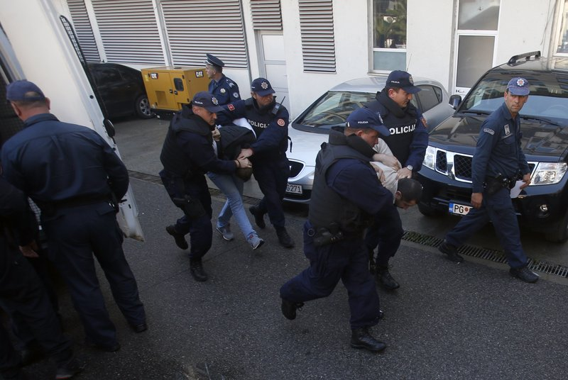 FILE - In this Sunday, Oct. 16, 2016 file photo, Montenegrin police officers escort people suspected of planning armed attacks after the parliamentary vote in Podgorica, Montenegro. (AP Photo/Darko Vojinovic, File)